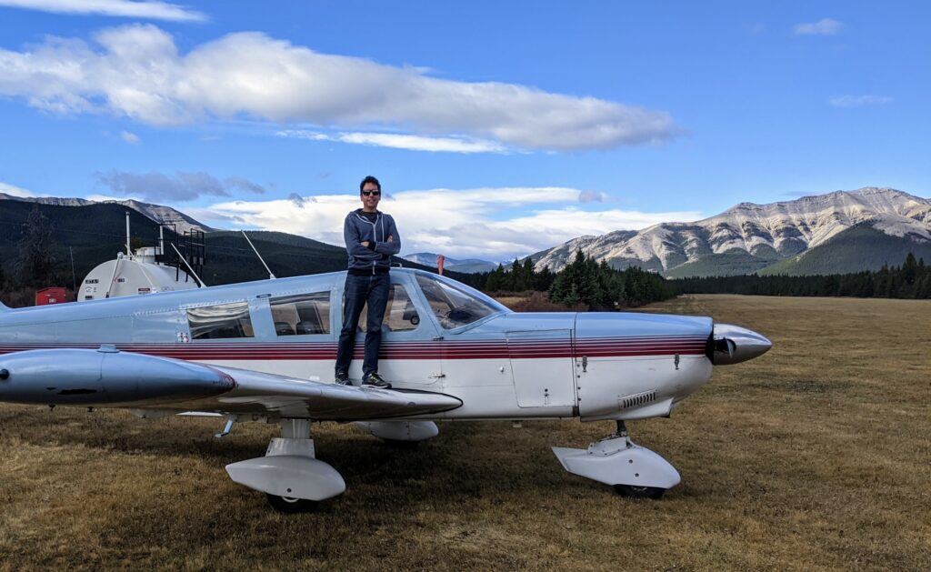 Blake standing on top of the wing of his new airplane.